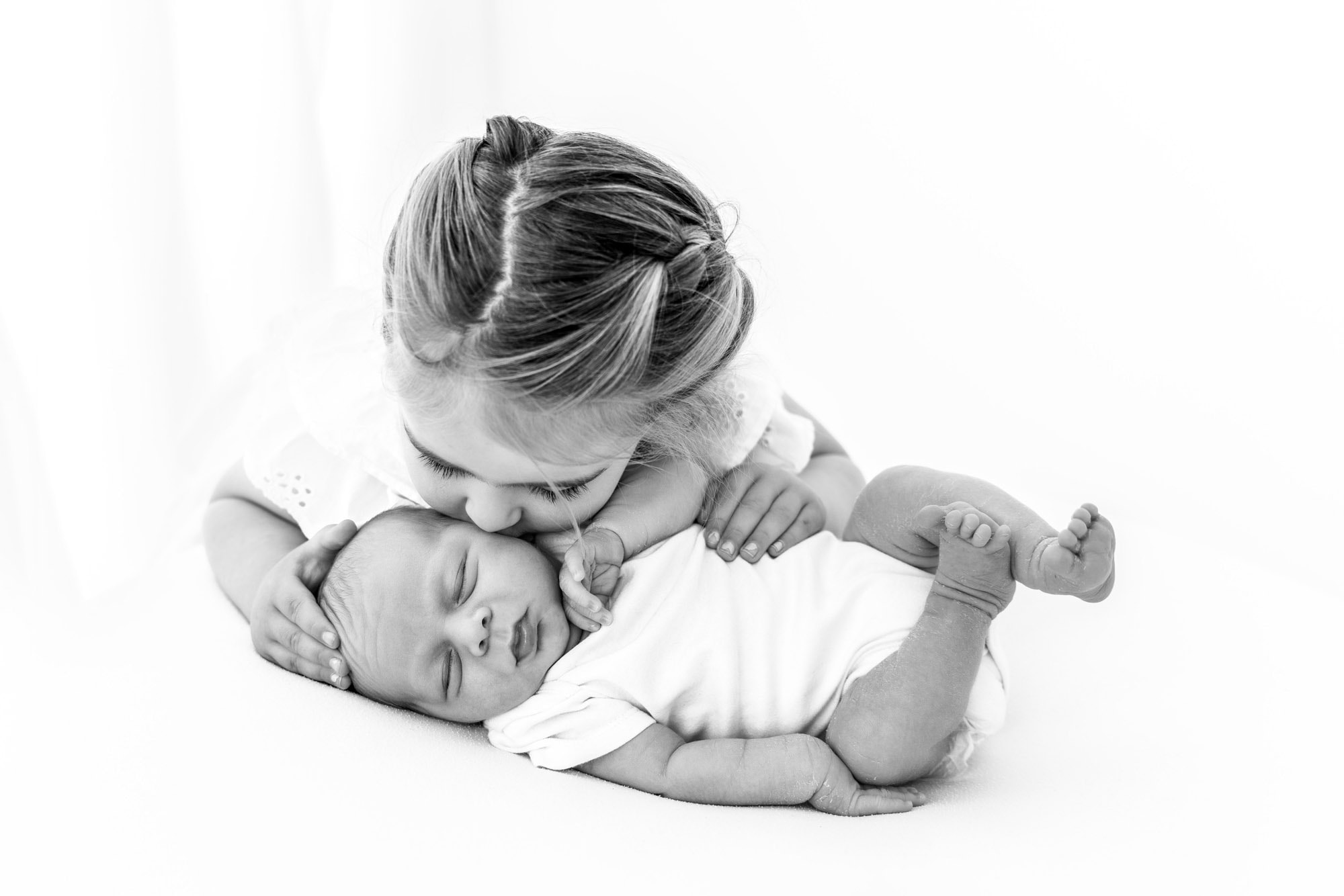 black and whiteimage of sibling kissing baby during session with norwich baby photographer