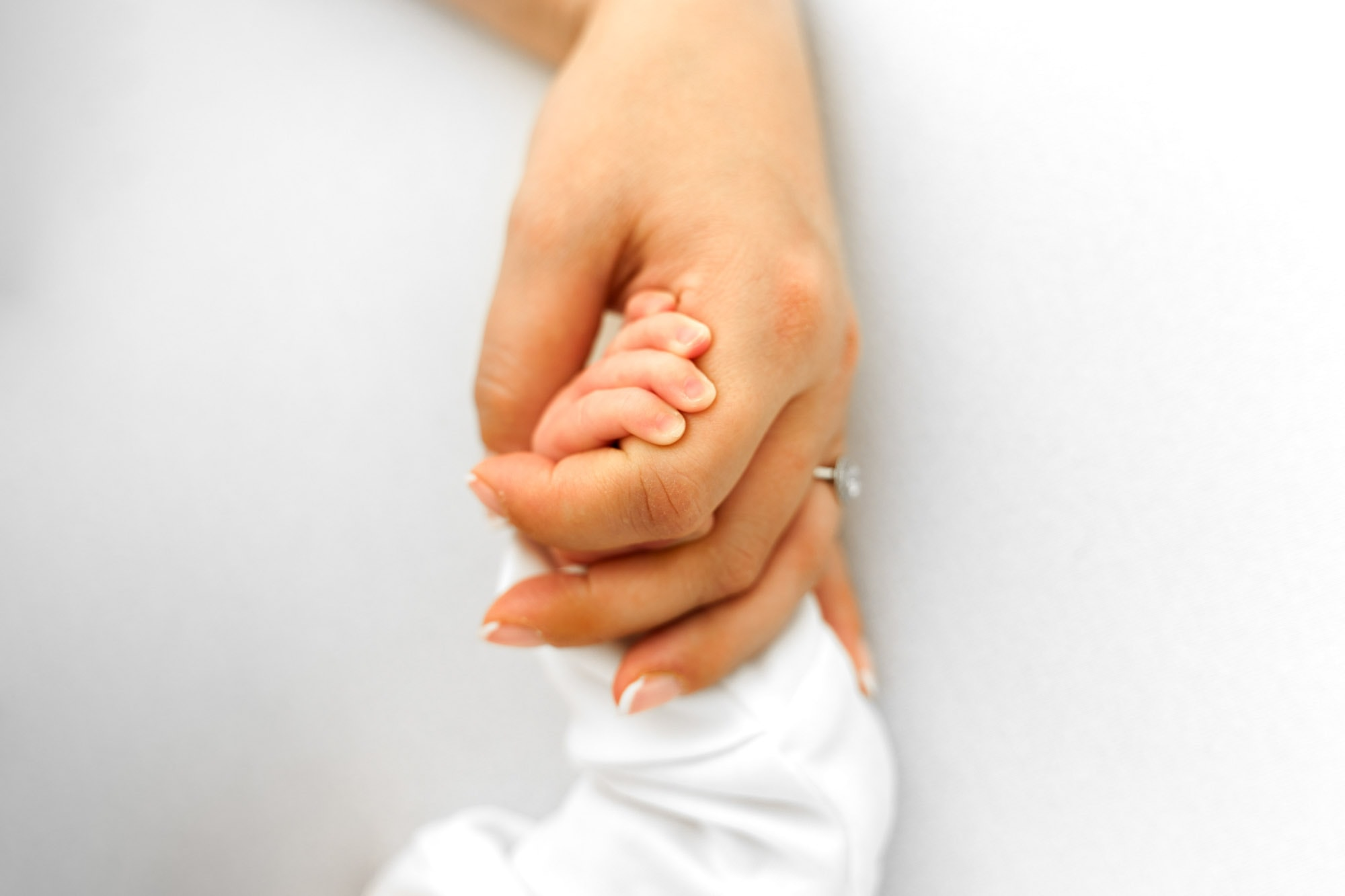 newborn photographer norwich captures close up of infants hand in mothers hand