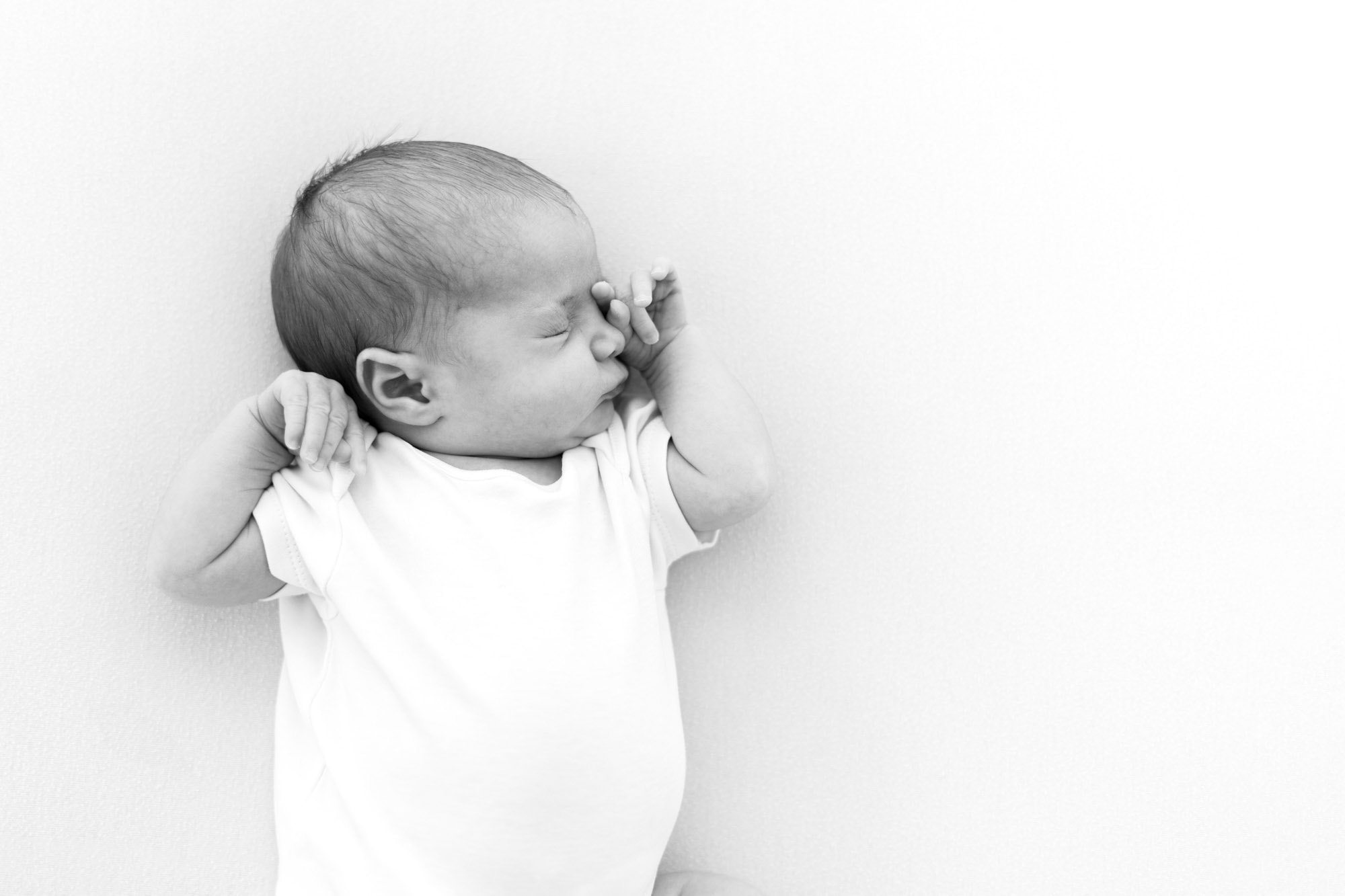 black & white image of baby stretching during session with norwich newborn photographer